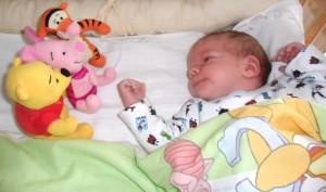 csecsemő figyeli az elé helyezett játékokat